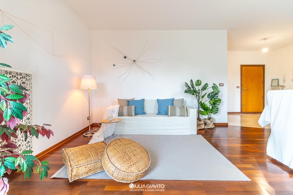 allestimento per la valorizzazione di una casa in vendita, soggiorno con pavimenti in parquet e marmo, divano tre posti bianco per Home Staging, arredare per far capire gli ingombri e gli spazi che si vanno ad acquistare
