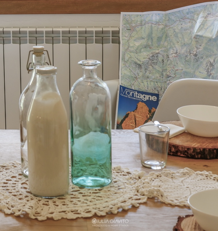 dettaglio tavolo in legno apparecchiato con rondelle di legno come sottopiatto, allestimento a Camporosso Tarvisio per appartamento in vendita