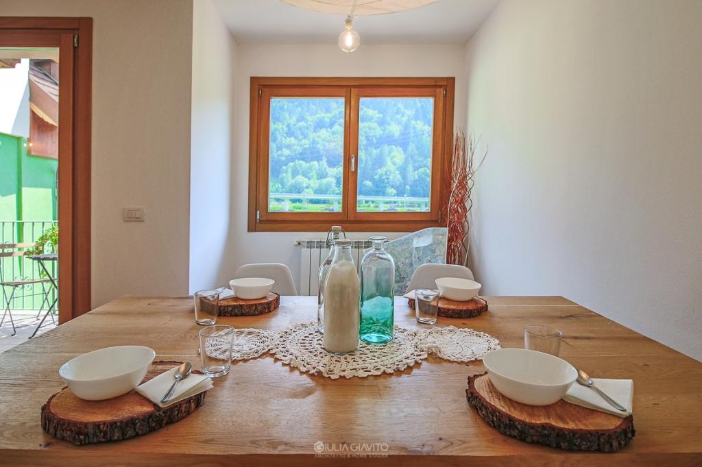 vista sulle montagne e  tavolo in legno apparecchiato con rondelle di legno come sottopiatto, allestimento a Camporosso Tarvisio per appartamento in vendita